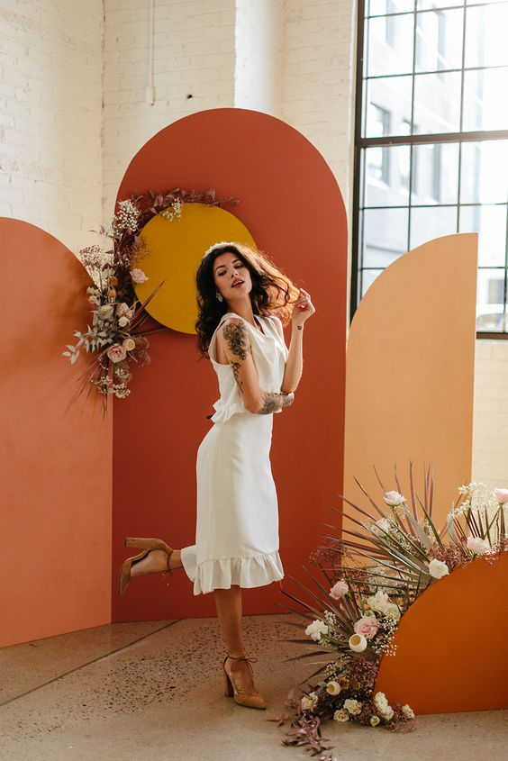 a bold color block wedding backdrop with white and pastel blooms and fronds is amazing for a 70s wedding