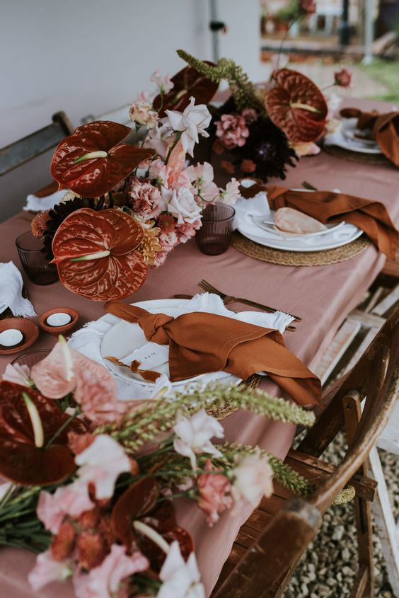a bright wedding tablescape with a rose tablecloth, pink, white and rust florals, rust napkins and terracotta candleholders