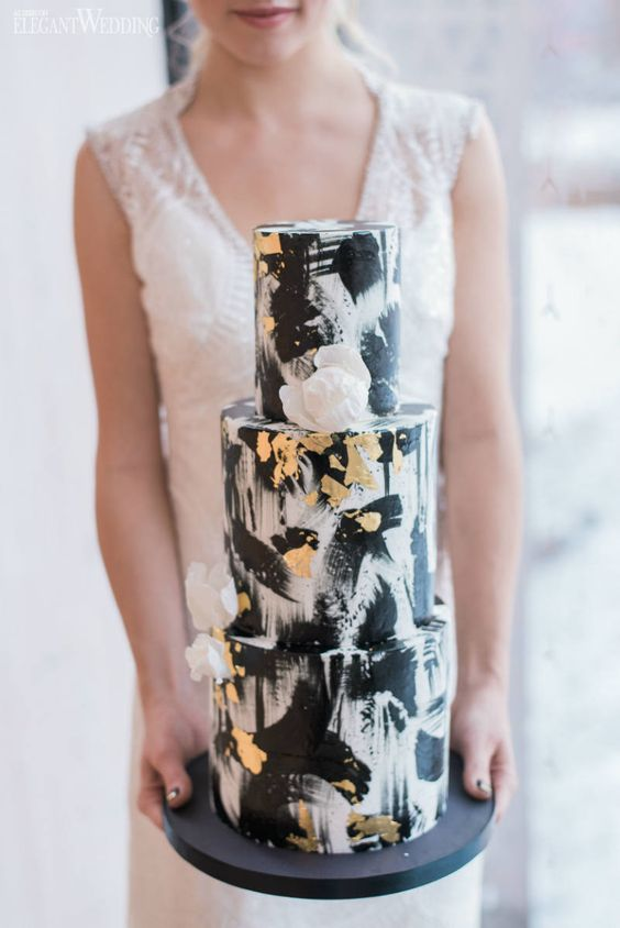 a glam white wedding cake all covered with black and gold brushstrokes and with white petals is chic
