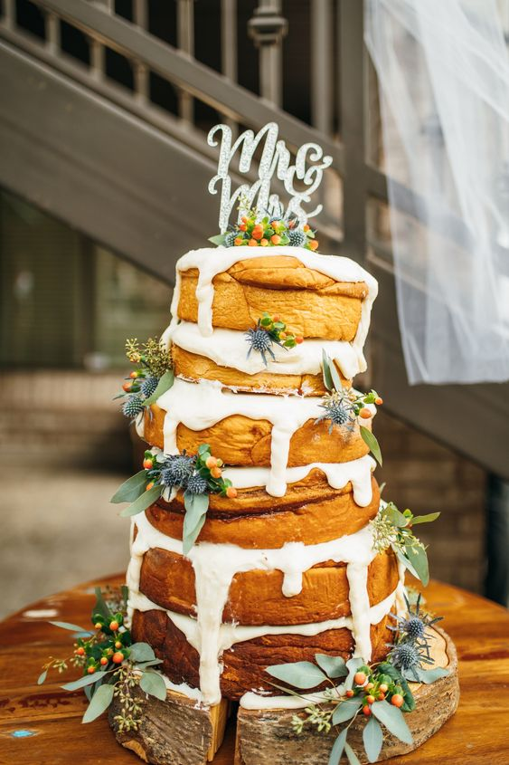 a large cinnamon roll wedding cake with white icing, decorated with berries, thistles and a calligraphy topper is all chic