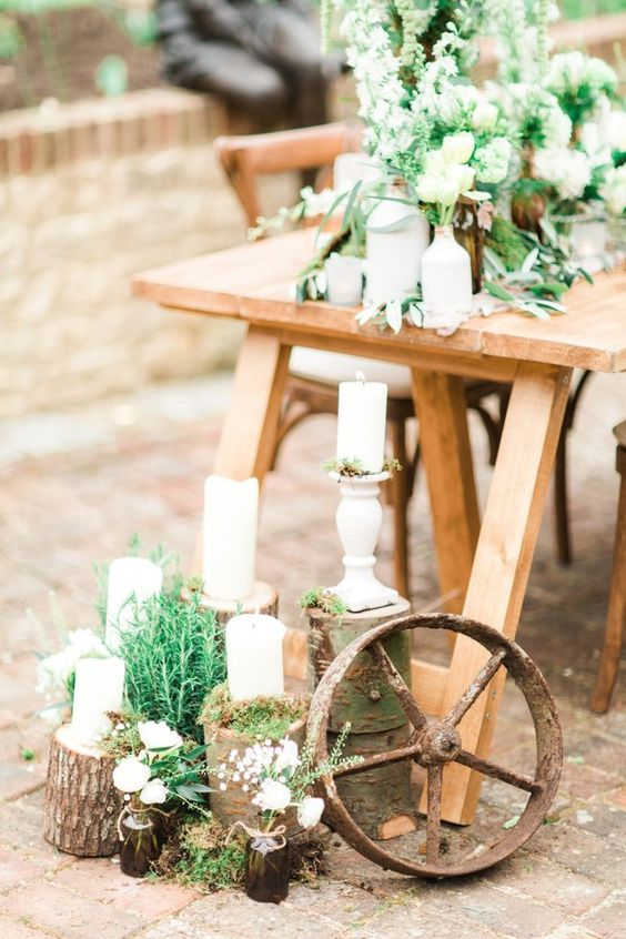 21 a lovely botanical wedding centerpiece with white blooms and greenery plus moss and tree stumps with candles and greenery on the ground