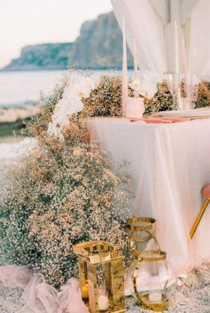 a lovely peachy, gold and blush baby's breath table runner with white orchids, blush candles and lovely candle lanterns in gold