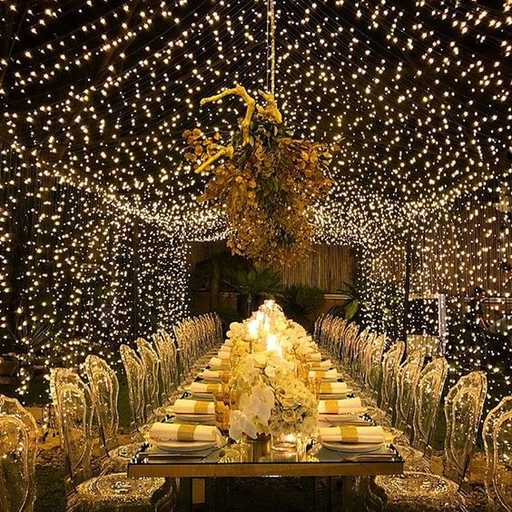 a luxurious wedding reception with a bold and sparkling light canopy and a hanging installation is a gorgeous idea