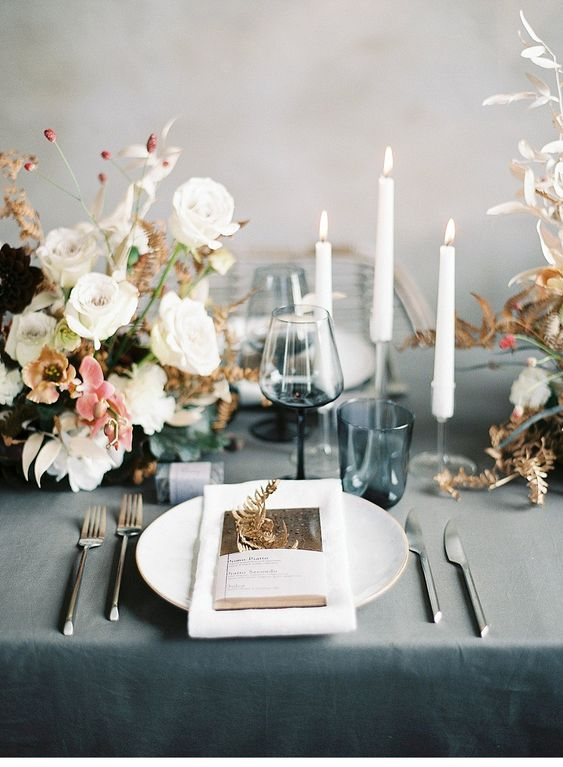 a stylish and chic Scandinavian wedding tablescape with a chic white floral centerpiece, candles, white porcelain and blue glasses