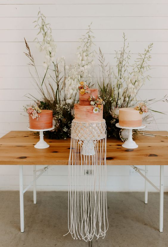 a trio of boho wedding cakes - a rust one with fresh blooms, a rust brushstroke with blooms and macrame and a color block rust and blush one with blooms