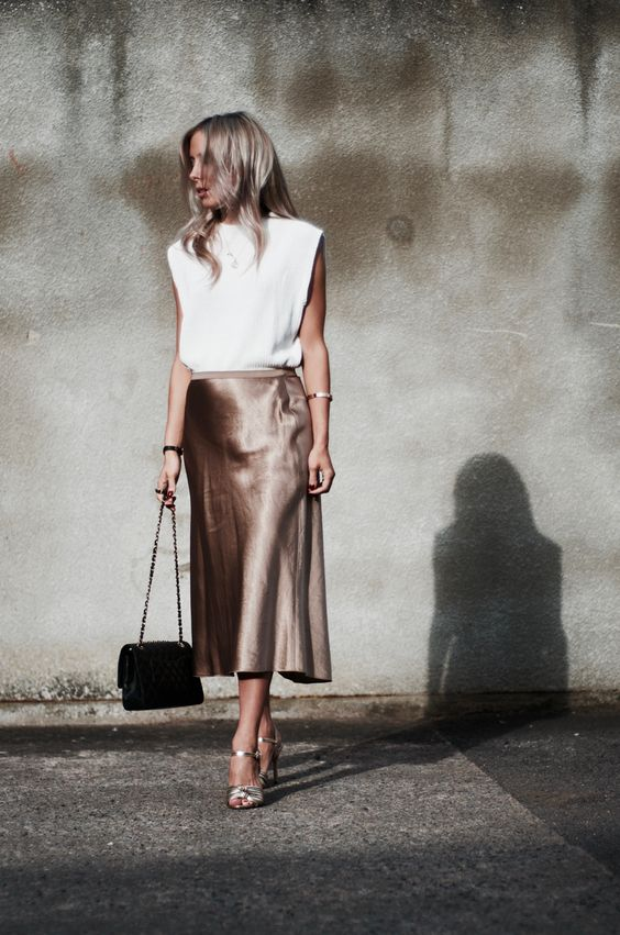 a white top with statement shoulders, an elegant taupe midi slip skirt, silver shoes and a black bag