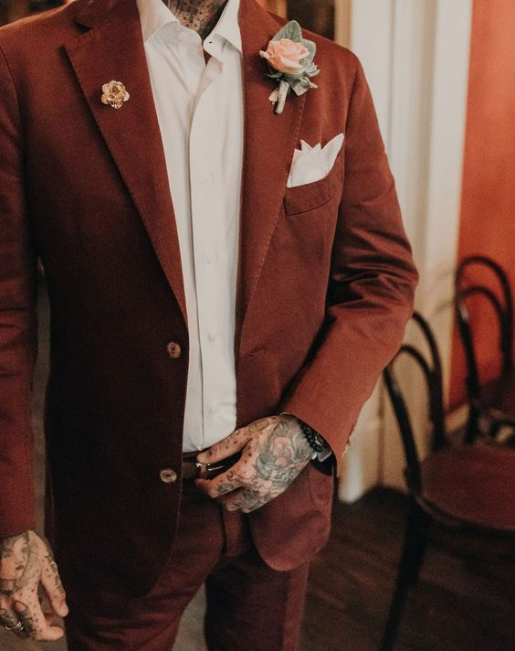 an elegant groom's look with a rust-colored suit, a white shirt, a blush floral boutonniere and a white pocket square