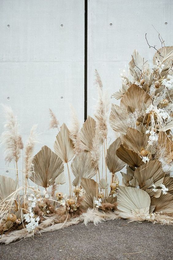 a boho tropical wedding altar with dried fronds, pampas grass, dried blooms and pampas grass is very chic and catchy