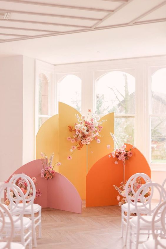 a bright and fun color block wedding backdrop with pink blooms and white foliage is a cheerful idea for a 70s wedding