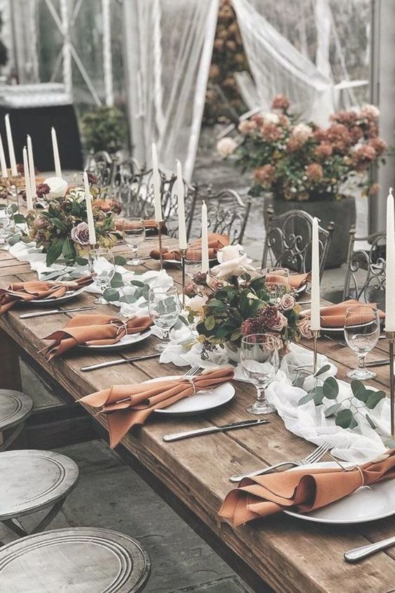 a chic wedding table setting with a white runner, pastel and white florals, rust napkins and candles