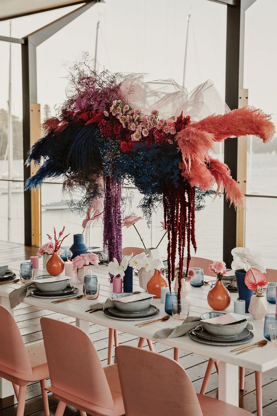 a colorful fresh and dried flower installation hanging over the table is a pretty idea to rock