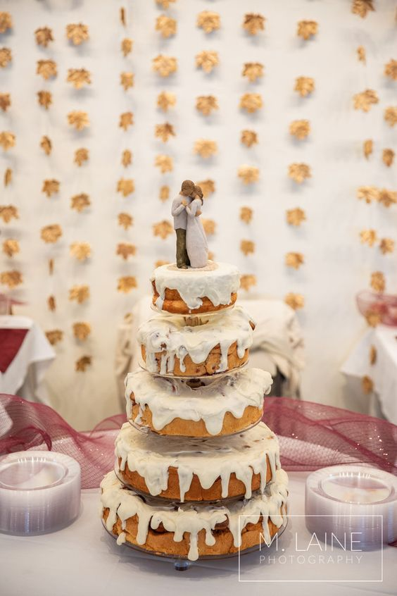 a lovely cinnamon roll wedding cake with white frosting and traditional toppers is a fresh look at a traditional wedding cake