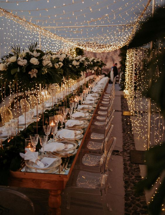 a luxurious wedding reception with gold touches, white linens, clear acrylic chairs, tall white centerpieces and a light canopy
