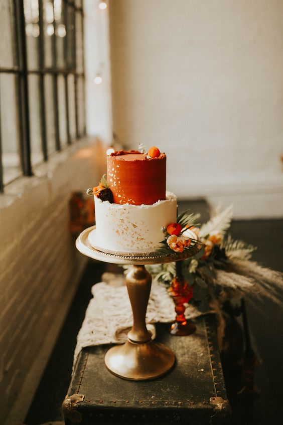 a two tone wedding cake with a rough edge, with a white and rust tier, gold leaf and fresh bright blooms and greenery