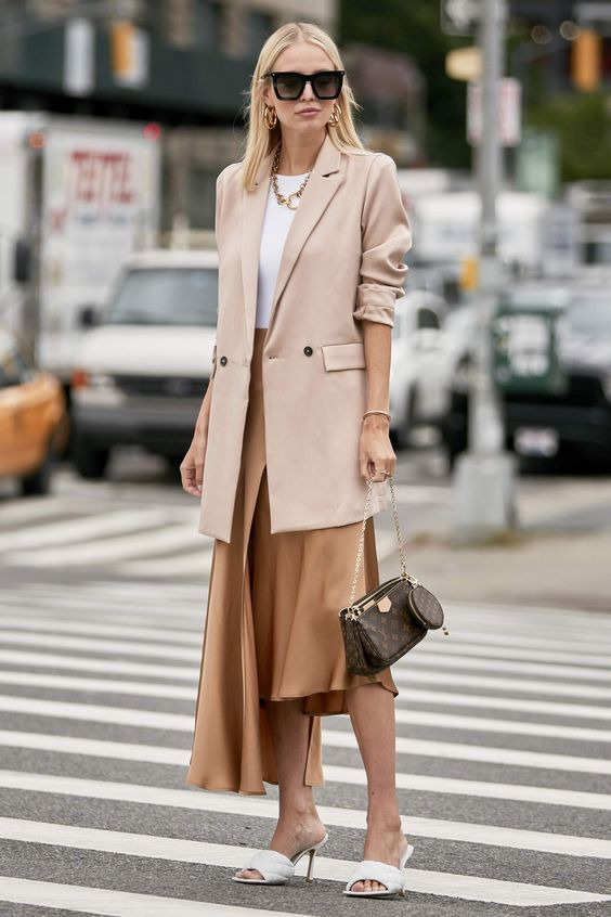 a white top, a chic asymmetrical skirt, white mules, a blush oversized blazer, statement accessories and a brown bag