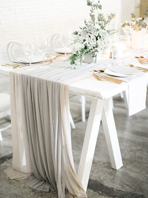 an airy and chic Scandinavian table setting with white and grey linens, gold cutlery, pale greenery and white blooms