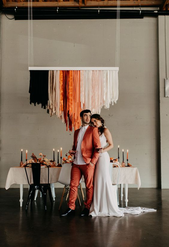 an orange suit, a white shirt, black shoes for a stylish modern wedding with a bold touch of color
