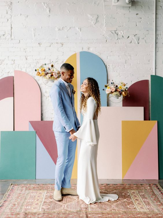 a bright color block wedding backdrop with embroidery hoops and bold blooms is a fun idea for a colorful 70s wedding