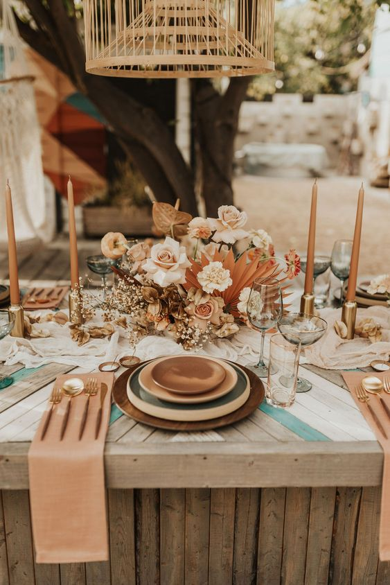 a chic wedding tablescape with layered plates, a lush blush and rust floral centerpiece, rust candles and rust napkins