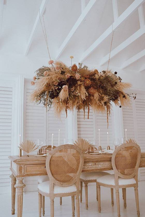 a dried flower and frond centerpiece with some herbs and foliage is a very pretty and neutral idea for a boho space
