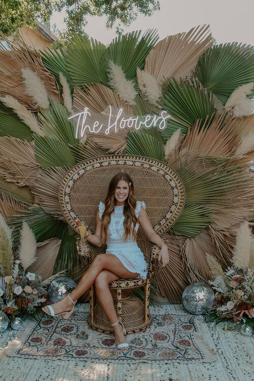 a dried palm leaf backdrop with fresh and dried leaves, pampas grass, a neon sign and disco balls for a boho disco wedding