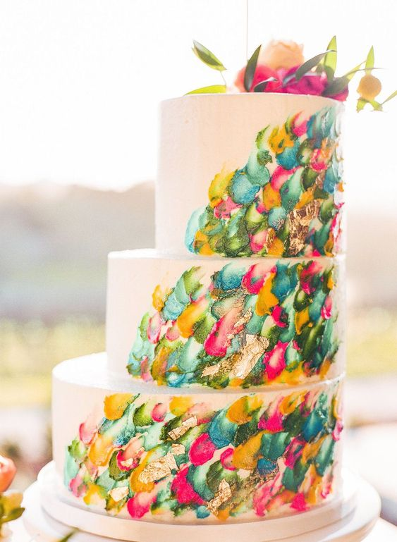 a jaw-dropping wedding cake with colorful brushstrokes and bold blooms on top is a very cool idea