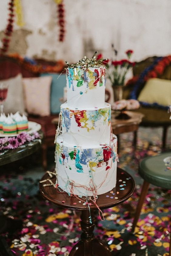 a lovely white wedding cake with bold watercolors and some gold leaf is an amazing idea for a summer or NYE wedding