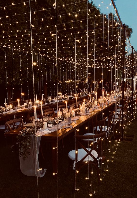 a modern and chic wedding reception space outdoors fully covered with fairy lights forming a canopy over it looks magical