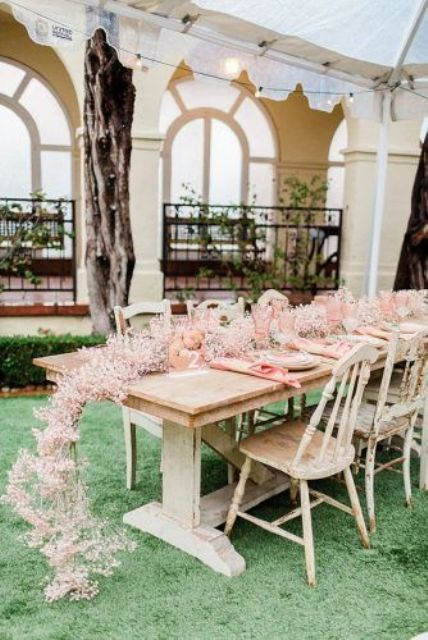 a pink baby's breath table runner, pink napkins and glasses is a very pretty and romantic idea to rock