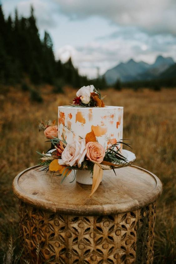 a white wedding cake with mustard and rust touches, with and pastel blooms and greenery plus fall foliage for a fall wedding