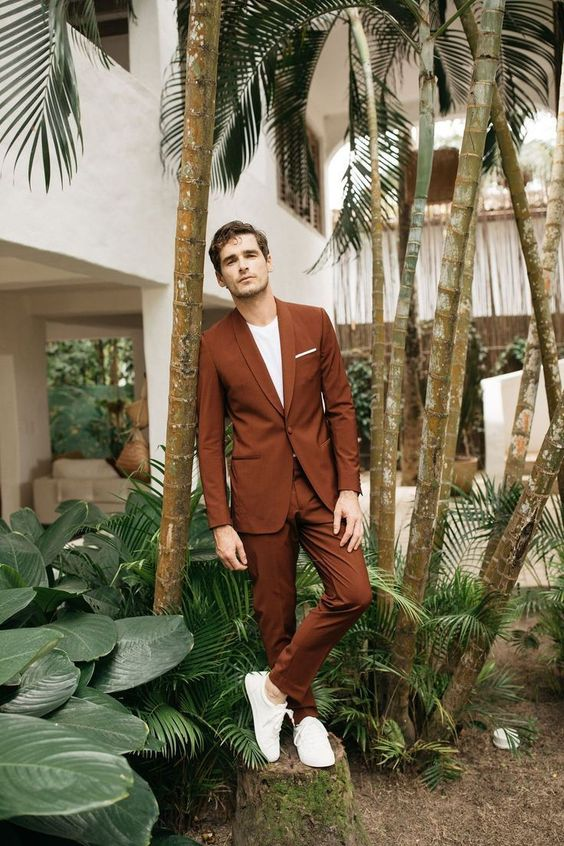 an ultra-modern groom's look with a rust-colored suit, a white t-shirt, white sneakers is very laconic and stylish