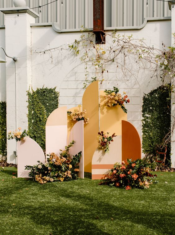 a bright color block wedding backdrop with greenery and bright blooms is a pretty idea for a boho 70s wedding