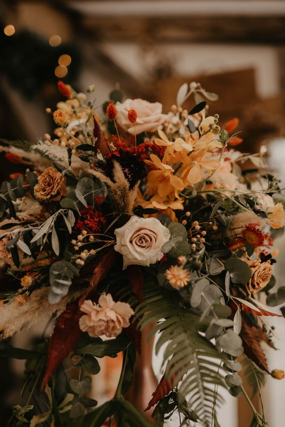 a dimensional floral arrangement with rust, peachy and red blooms, greenery and grasses is amazing for a fall wedding