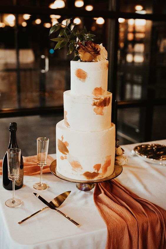 a white wedding cake with rust and amber brushstrokes, with a white and rust rose and greenery on top is pure chic