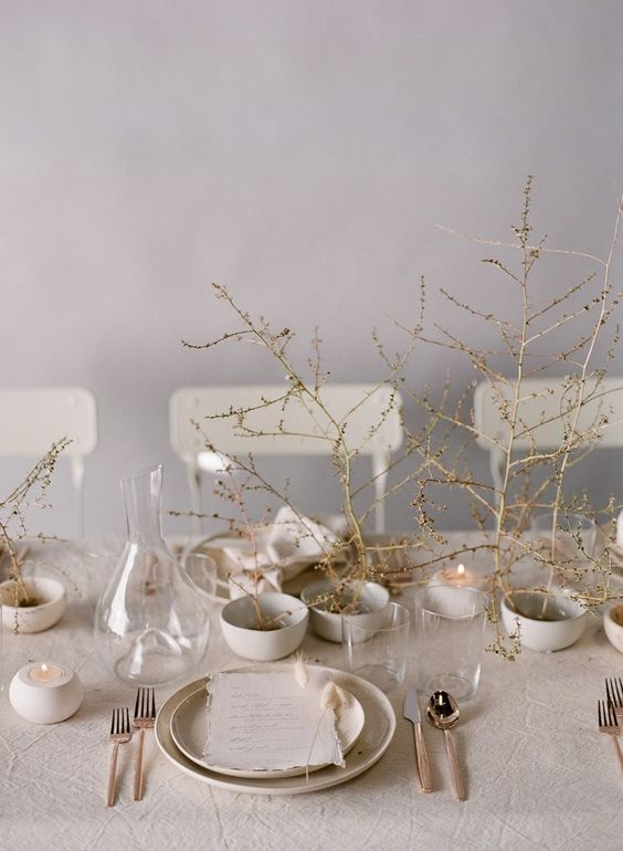an ethereal Scandinavian spring tablescape with branches, neutral porcelain, candles and simple linens
