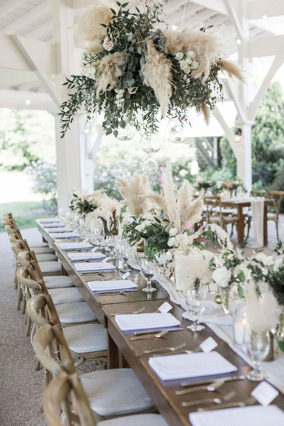 a boho installation of greenery. blush roses and pampas grass paired with matching centerpieces is amazing