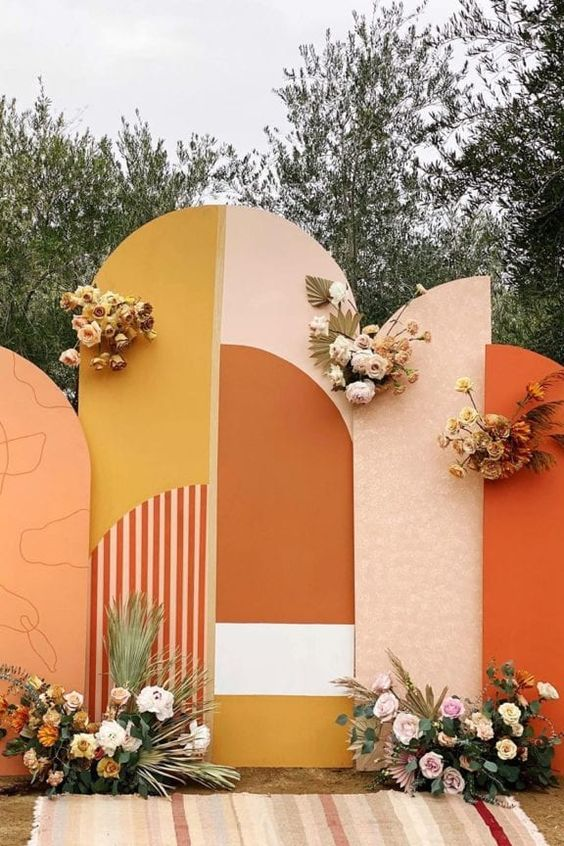 a bright color block wedding backdrop with some prints, pastel and neutral blooms and foliage is chic