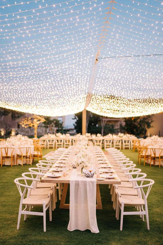 a neutral and very stylish wedding reception with an oversized light canopy that is really jaw-dropping and raises the mood