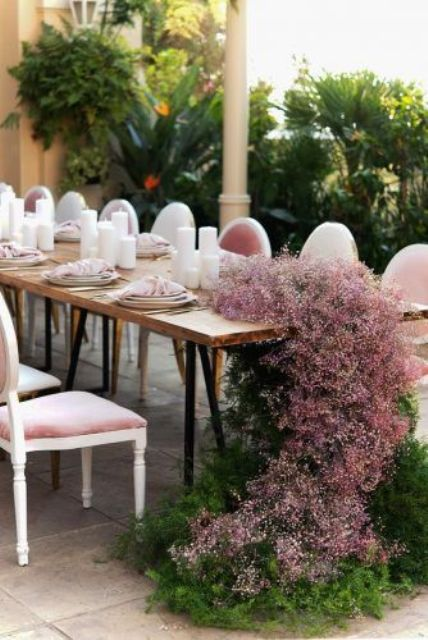 a pretty wedding table runner with pink baby's breath and greenery, pink chairs and napkins make the space very chic and pretty