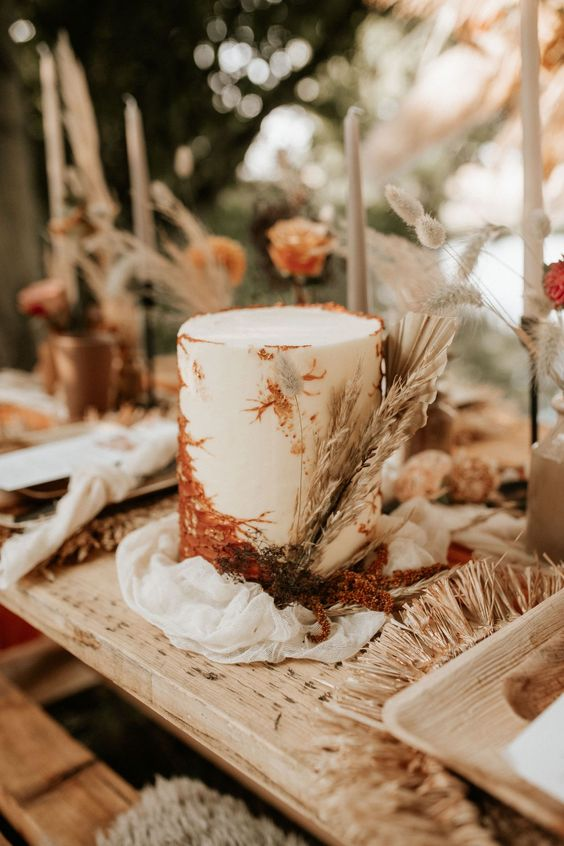 a white wedding cake with rust sugar decorating and dried grasses and fronds is a lovely idea for a boho wedding