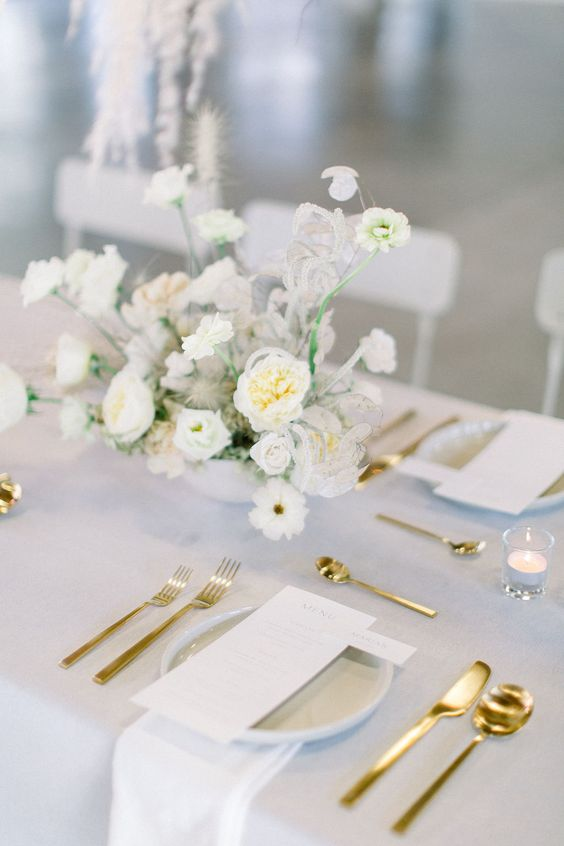 an ethereal spring wedding tablescape with neutral linens, gold cutlery, a white floral centerpiece and white stationery