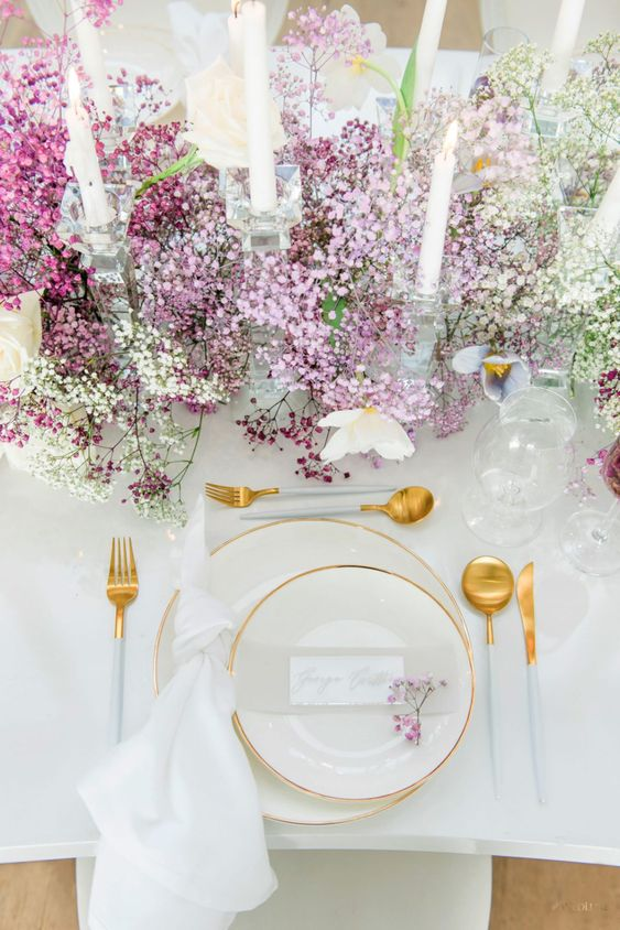 a beautiful ombre white to lilac and purple table runner and white candles make the tablescape very refined and very chic