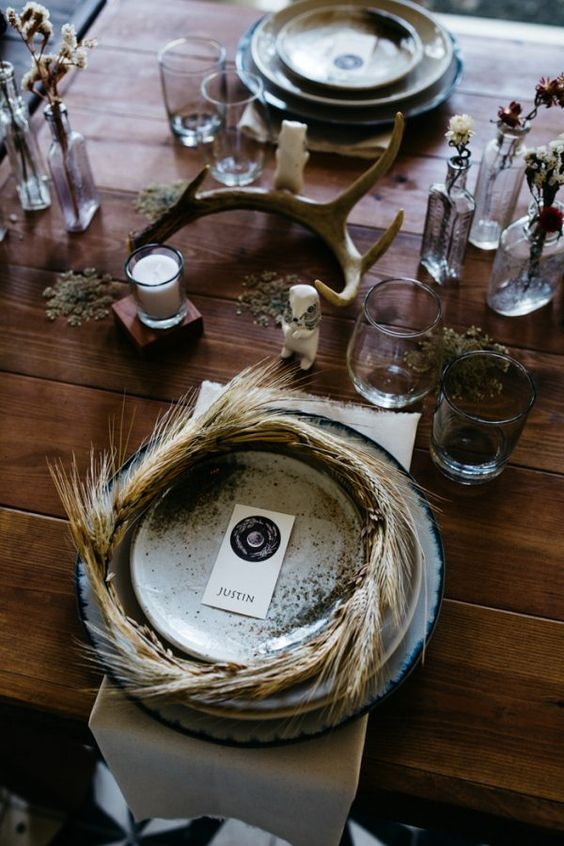 a creative fairy-tale Scandinavian wedding tablescape with antlers, greenery, smoked glasses, wheat wreaths and candles