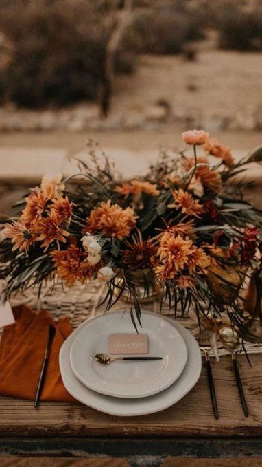 a fall boho wedding tablescape with a macrame runner, a rust-colored floral centerpiece, rust napkins and stylish cutlery
