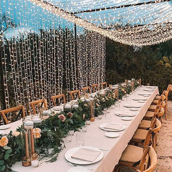 a pretty neutral wedding reception with greenery and blooms and a light canopy over it for a lovely look