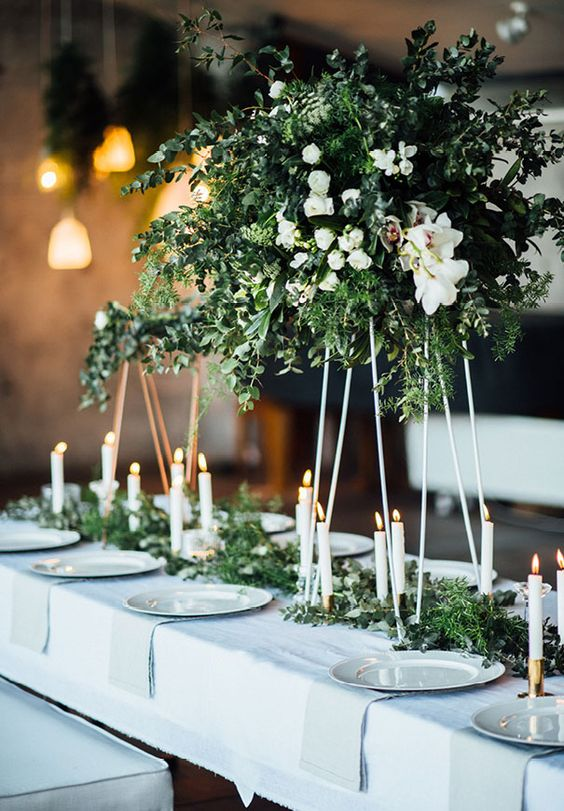 a spectacular tall wedding centerpiece of greenery and white blooms plus a matching greenery runner on the table and candles