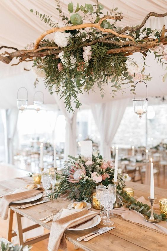 a wild and boho overhead installation of driftwood, neutral blooms and lots of greenery hanging down plus a matching small centerpiece