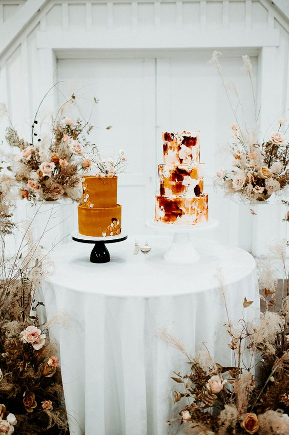 an orange wedding cake decorated with sugar petals and dried blooms on top and a brushstroke wedding cake in white, burgundy and orange for a boho wedding