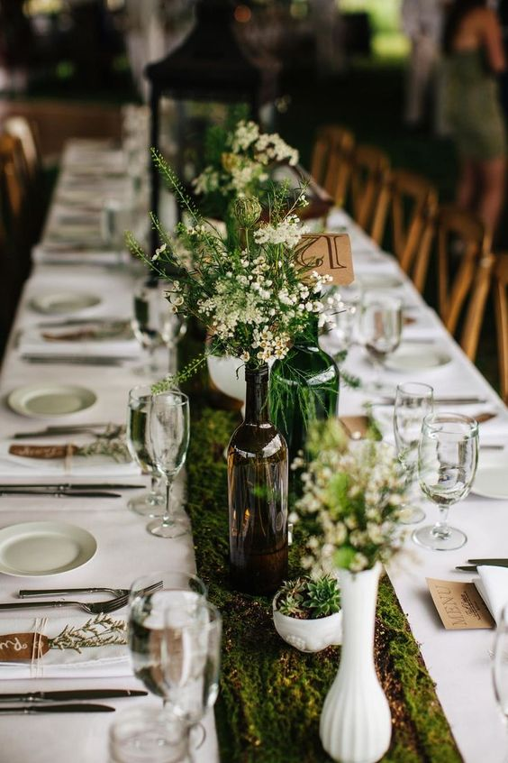 a fresh spring wedding tablescape with a moss runner, bottles and vases with greenery and wildflowers and white linens