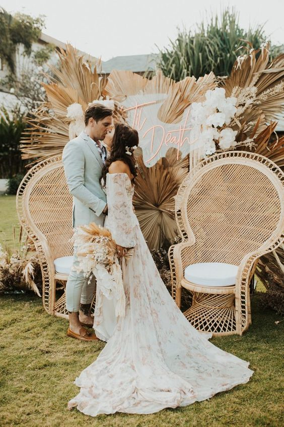 a gorgeous boho wedding backdrop with dried fronds, white blooms and a neon sign and peacock chairs to match the look